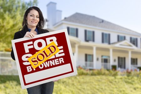 Smiling Hispanic Female Holding Sold For Sale By Owner Sign In Front of Beautiful House.